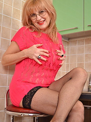 Mature lady playing in the kitchen